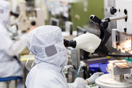 clean room: Operator in factory use microscope Stock Photo