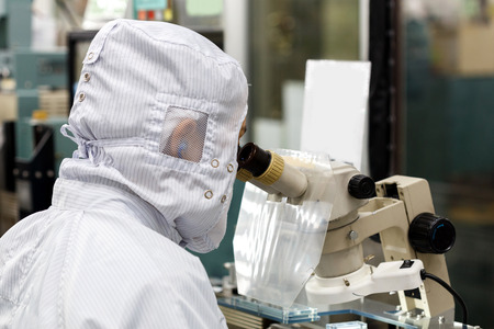 Operator in factory use microscope 스톡 콘텐츠