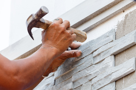 worker install stone wall surface with cement for house  photo