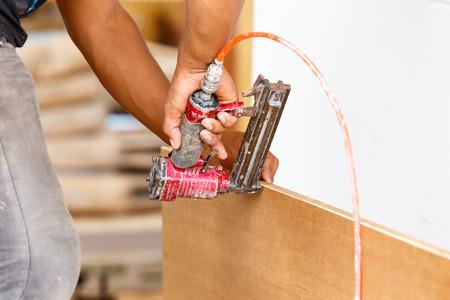carpenter use air-gun for make new furniture  photo