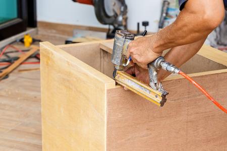 airgun: carpenter use air-gun for make new furniture
