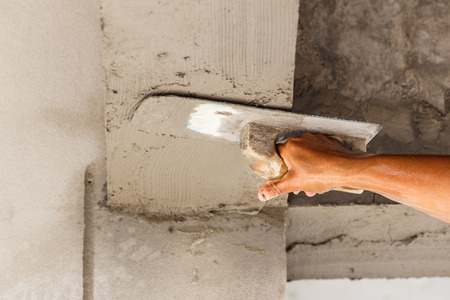 the concrete: plasterer concrete on wall of house construction Stock Photo