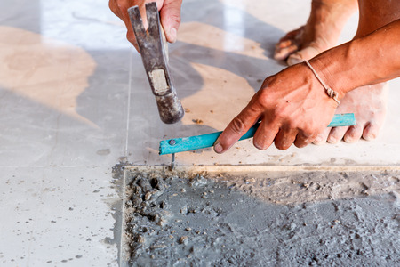 Labor installing tile floor for new house building photo