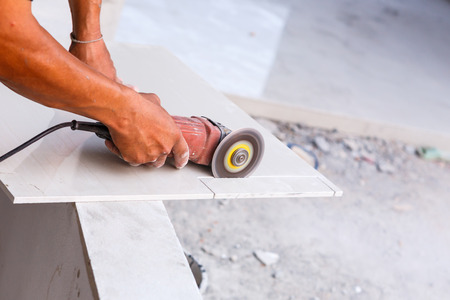 Labor cutting tile floor for new house building photo