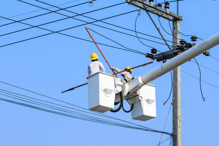 electrician working on electric pole photo