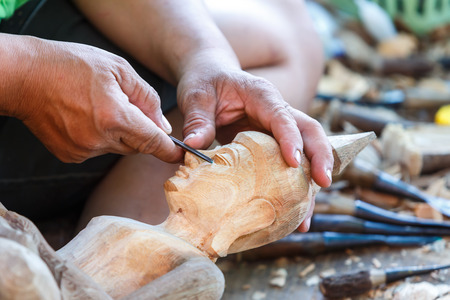 Hand of carver carving wood photo