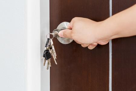 unlocking: Locking or unlocking door with key by hand Stock Photo