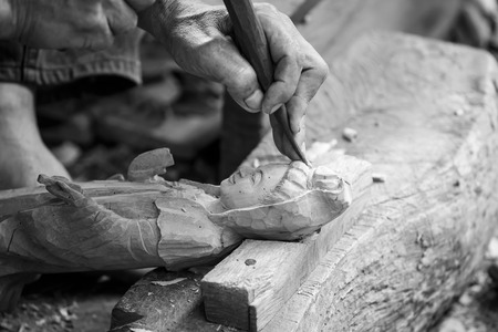 engraver: Hand of carver carving wood in blackand white color tone Stock Photo