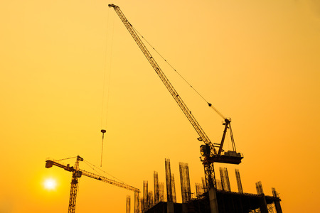 infrastructure buildings: Construction site with cranes on silhouette background Stock Photo