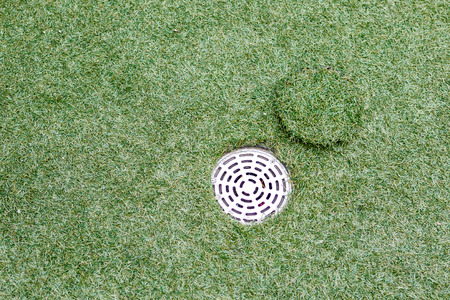 drain water: artificial grass with drain water Stock Photo