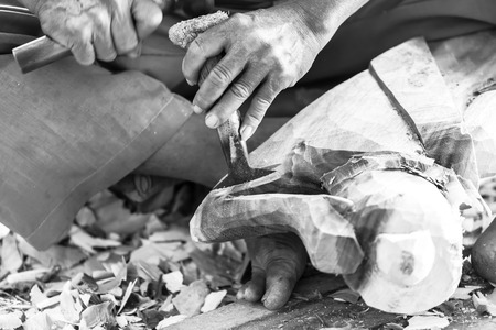 carver: Hand of carver carving wood in black and white color tone