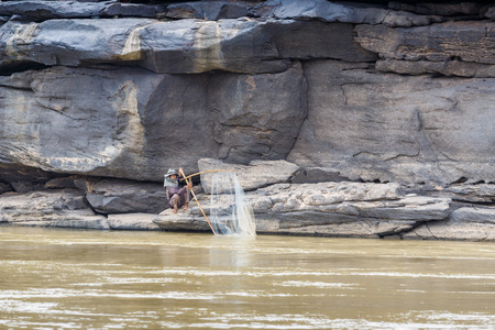 khong river: LAO - MARCH 27 2015: Local fisherman catch fish in khong river at Thailand and Lao border on March 27, 2015.