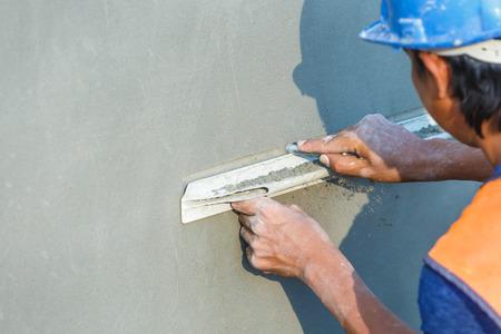 plasterer: plasterer concrete worker at wall of house construction