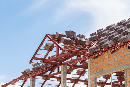 roof: roof under construction with stacks of roof tiles for home building