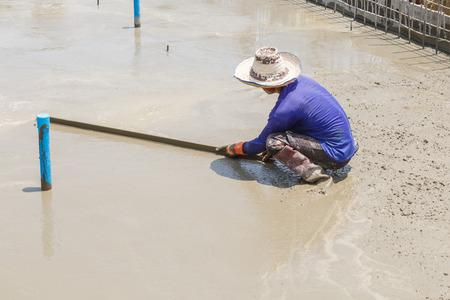 plasterer: plasterer concrete worker at floor of house construction