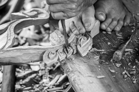 engraver: Hand of carver carving wood in black and white color tone