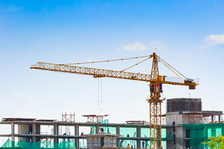 construction sites: Building crane and construction site under blue sky Stock Photo