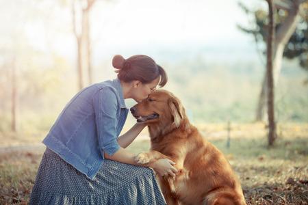 Hermosa mujer con un perro retriver de oro linda Foto de archivo
