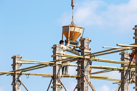 dangerouse: Worker working in construction on blue sky