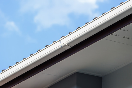 roofing: White gutter on the roof top of house