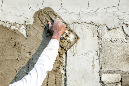 plasterwork: plasterer concrete worker at wall of house construction