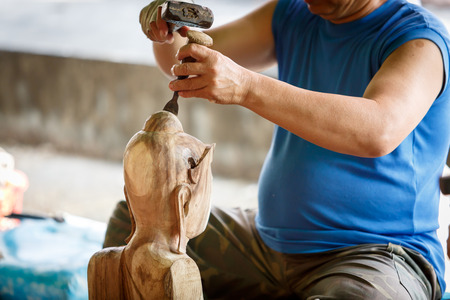 engraver: Hand of carver carving wood Stock Photo
