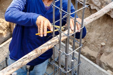 medieval blacksmith: worker bending steel rod for construction job Stock Photo