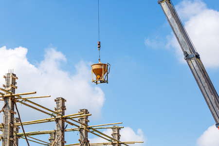 dangerouse: Crane working in construction on blue sky Stock Photo