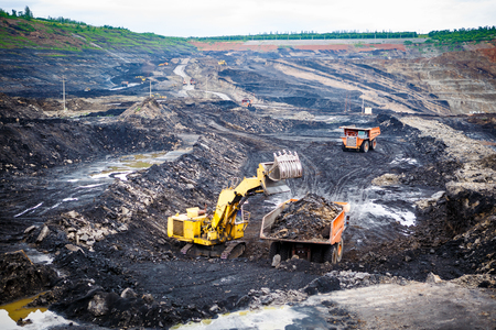 Mining dump trucks working in Lignite coalmine Stock Photo