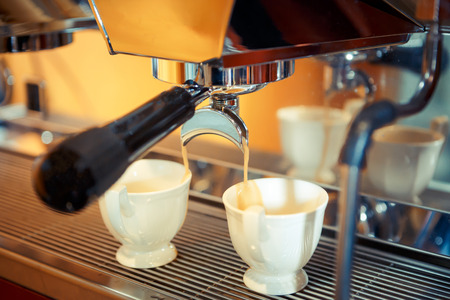 espresso machine pouring fresh coffee into cups