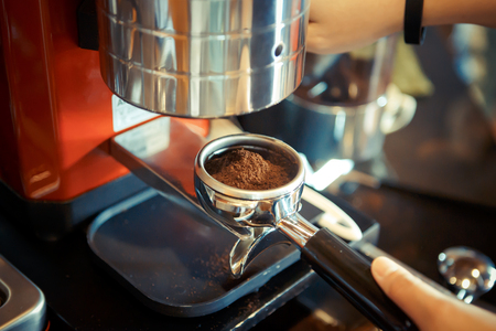 barista presses ground coffee using tamper toned