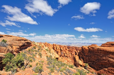 Two Hikers Hiking along the ridge in Arches National Park, Utah, USA photo