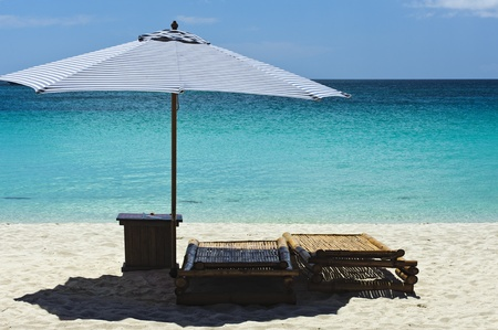 Tranquil Beach Scene with Lounging chairs overlooking a clear blue sea and sky. Stock Photo