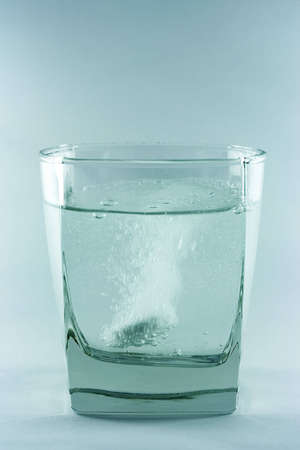 An aspirin tablet sinking in the glass with water. Stock Photo - 669173
