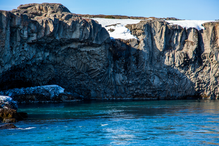 Columnar basalt formation over turquoise water with sunny weather in iceland