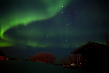 Dancing polar lights with bungalow in the foreground in winter in Iceland Stockfoto - 124810236
