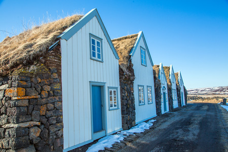 Grass-roofed huts with white front, currently a museum in Iceland Stockfoto - 124810237