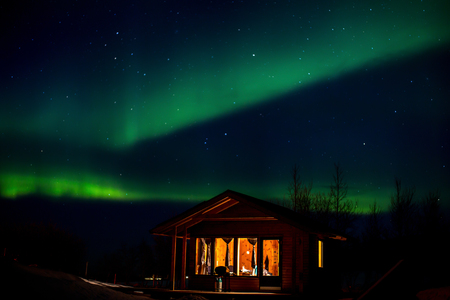 Dancing polar lighDancing polar lights with bungalow in the foreground in winter in Icelandts, bungalow the foreground