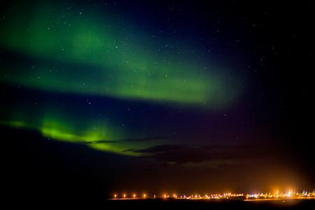 Aurora boreale o aurora boreale su una città in Islanda Archivio Fotografico