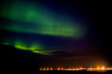 Northern lights or aurora borealis over a city in Iceland