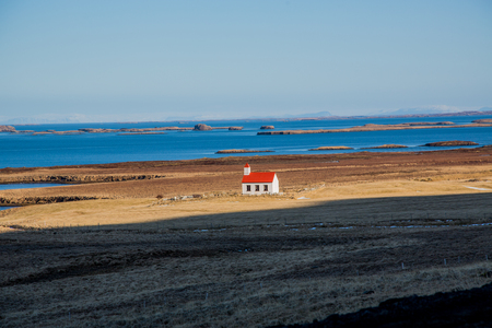 Lonely church with cemetery in front of the sea in Iceland Stockfoto - 124810245