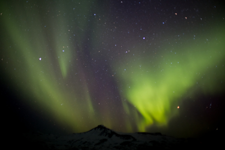 Northern lights or polar lights over a mountain in winter in Iceland