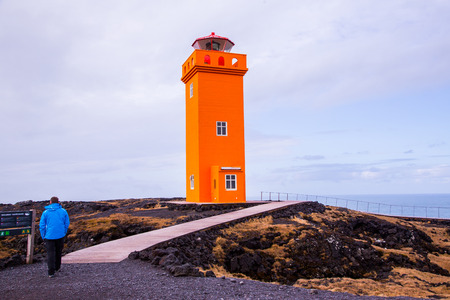 Orange lighthouse with human in the foreground, Iceland Stockfoto