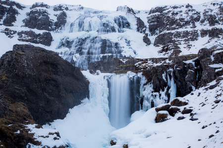 Dynjandi waterfall in winter with fog effect in iceland