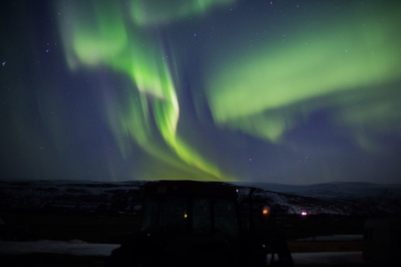 Northern lights with tractor in foreground in Iceland Stockfoto