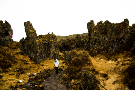 Woman wanders through lava stone formations in the winter in Iceland Stockfoto