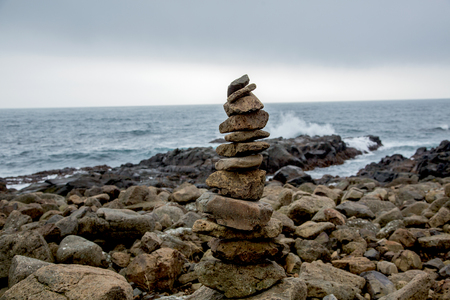 Cairn in front of coastal landscape at stormy weather in Iceland Stockfoto