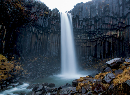 Svartifoss waterfall surrounded by basalt columns in southern Iceland, mystical veil effect