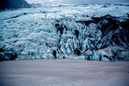 Solheimajokull glacier with blue ice with black ash inclusions Stockfoto - 124810307