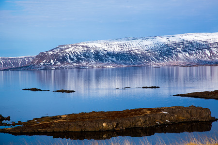 Icelandic fjord reflected in the water with stones in the foreground in best weather